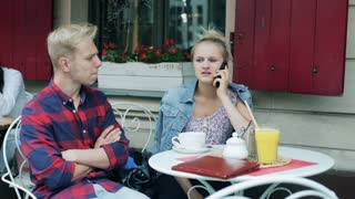 Couple talking on cellphone in the cafe and receiving bad news