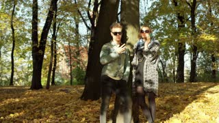 Couple using electronics and standing next to the autumnal tree