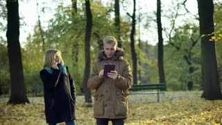 Couple using electronics in the autumnal park