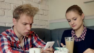 Couple using electronics in the cafe and relaxing