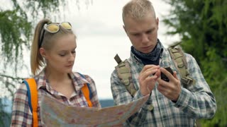 Couple using map and compass while checking the direction in the forest