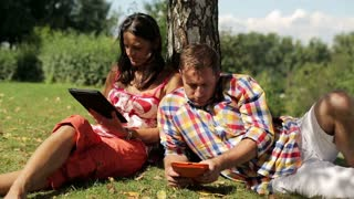 couple using their tablets and sitting under the tree