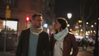 Couple walking at night on the street, steadycam shot