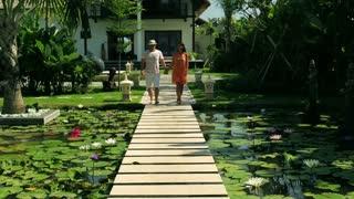 Couple walking on footbridge in exotic garden and holding hands
