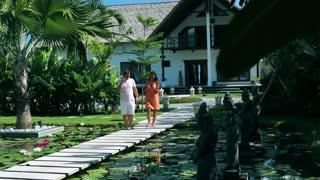 Couple walking on footbridge in exotic garden and talking on cellphones
