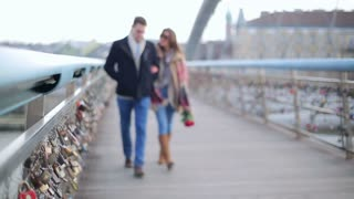 Couple walking on the bridge and smiling to the camera
