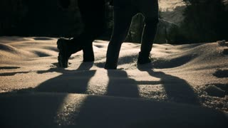 Couple walking together on the snow, steady, slow motion shot at 240fps