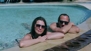 Couple waving hands and smiling to the camera, swimming pool steadycam shot