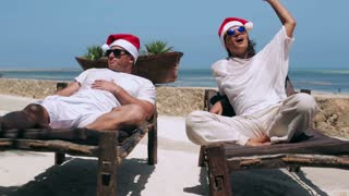 Couple wearing santas hat and lying on sunbeds