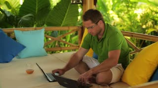 Couple working on laptops in the garden, steadycam shot