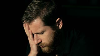Depressed man with ginger beard looking very worried