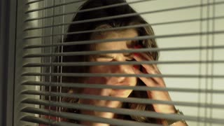 Depressed woman crying and standing next to the window