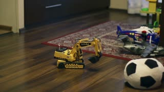 Digger toy moving on the floor, steadycam shot, slow motion