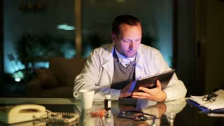 Doctor working on tablet at night in office by the desk.