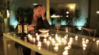 drunk man sitting by the table and drinking wine after unsuccessful date