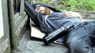 Drunk man waking up while lying on the ground and looking around, steadycam shot