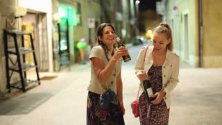 Drunk women with bottle of vine standing on the street in the evening