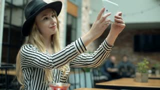 Elegant woman in black hat doing selfies on tablet in the cafe