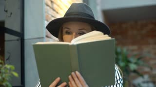 Elegant woman listening music and reading book while smiling to the camera