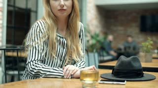 Elegant woman looking thoughtful while sitting in the cafe, steadycam shot