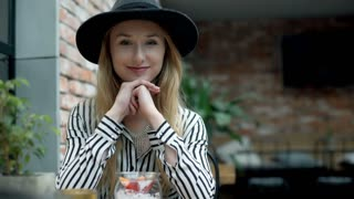 Elegant woman relaxing in the cafe and smiling to the camera