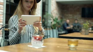 Elegant woman sitting in the cafe and doing photos on tablet, steadycam shot