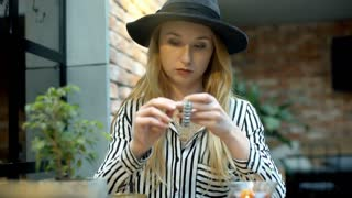Elegant woman sitting in the cafe and tries to set time on her silver watch