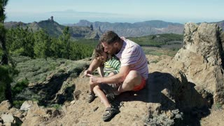 Father and son browsing internet on smartphone while sitting on the rock in moun