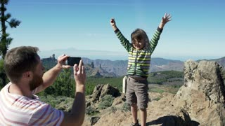 Father doing photo of his son on smartphone in the mountains