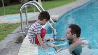 Father talking with his son in the swimming-pool