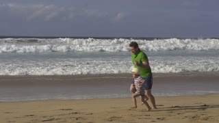 Father with his son jogging on the beach, slow motion shot at 240fps