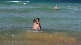 Father with his son playing in the sea, slow motion shot at 240fps