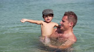 Father with little son playing in the sea, slow motion shot at 120fps