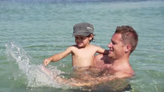 Father with little son playing in the sea, slow motion shot at 240fps