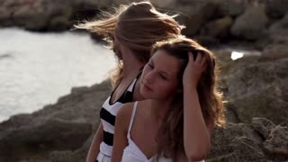 Female friends fluttering their hair on the seashore, slow motion shot at 120fps
