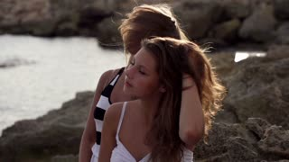 Female friends fluttering their hair on the seashore, slow motion shot at 240fps