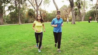 Female friends running in the park and smiling to the camera, steadycam shot