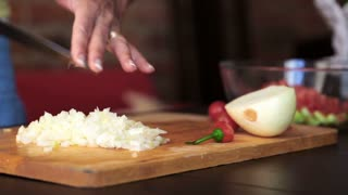 Female hands with knife chopping fresh onion