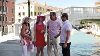 Four happy rich friends with shopping bags in Venice