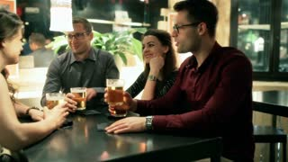 Friends drinking beers and chatting in the pub, steadycam shot