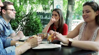 Friends eating lunch in the outdoor cafe and chatting, steadycam shot