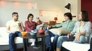 Friends laughing in the flat and chatting with each other