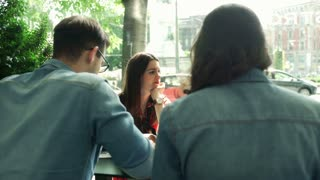 Friends relaxing in the outdoor cafe, steadycam shot