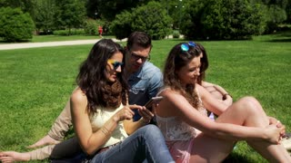 Friends sitting in the park and browsing internet on smartphone, steadycam shot