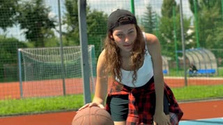 Girl bouncing the basket ball and looking to the camera on sports field