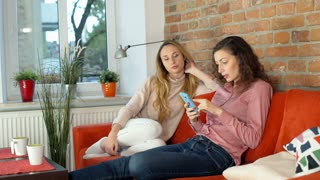 Girl browsing internet on smartphone and showing something to her friend