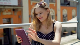 Girl browsing internet on tablet and smiling to the camera in the city