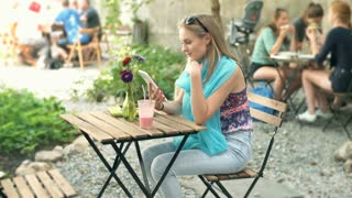 Girl browsing internet on tablet and smiling to the camera in the outdoor cafe