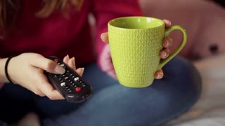 Girl changing channels on TV using remote control and drinking beverage