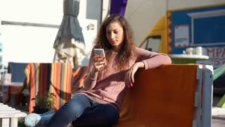 Girl checking time on smartphone and waiting for someone outdoors
